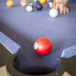 Playing pool on a pool table with billiard balls